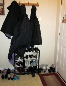 small foyer with a coat and a shoe rack