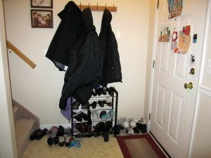 small foyer with a coat rack and a shoe rack