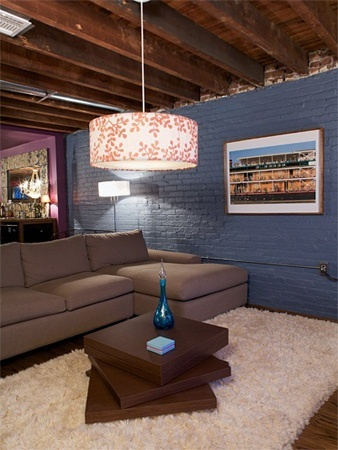 Unfinished basement with painted blue walls and laminate floor