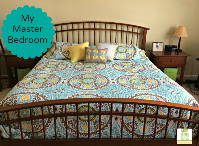 king sized bed with medallion bedspread in blue, green and yellow