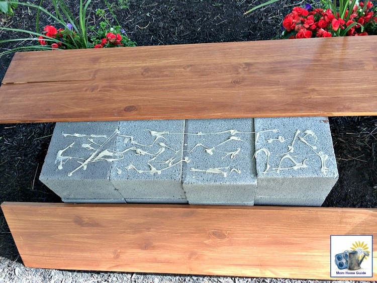 Use landscape adhesive to glue wood boards to the top of a stack of cinder blocks to create a study and inexpensive bench!