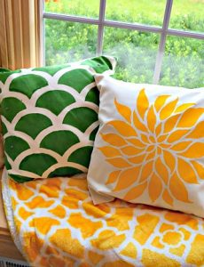 Beautiful window seat with a colorful thrown and stenciled pillows