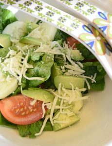 Fresh tomato, spinach and avocado salad with shredded mozzarella cheese
