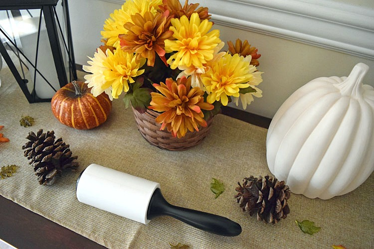 Using a Scotch-Brite™ Lint Roller to clean dust off a table runner
