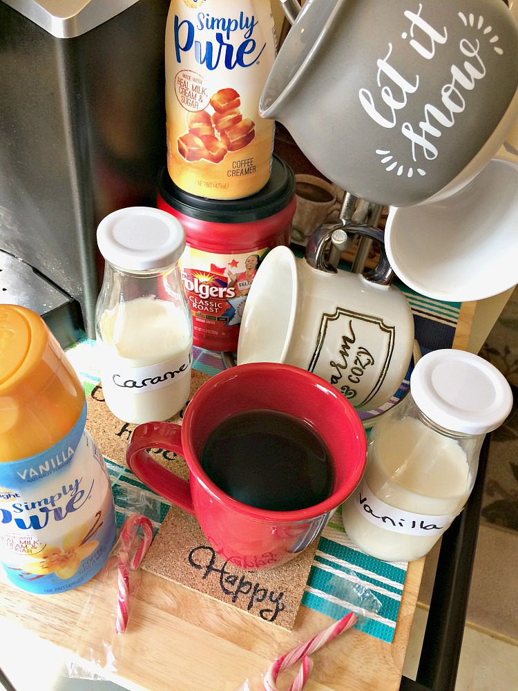 A holiday coffee bar with Christmas mugs and flavored creamers.