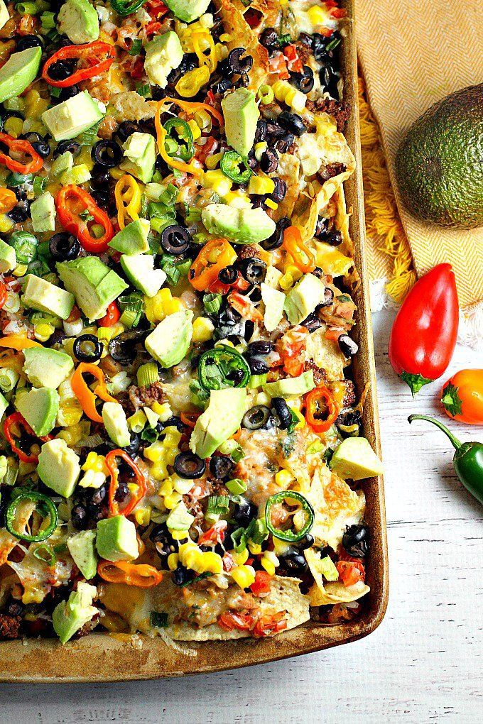 Recipe for loaded nachos with beef, beans, avocado and mini peppers.