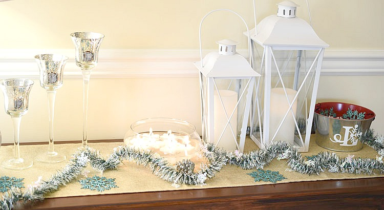 Christmas console table with white lanterns, frosted pine, tall glass votive candles and floating candles