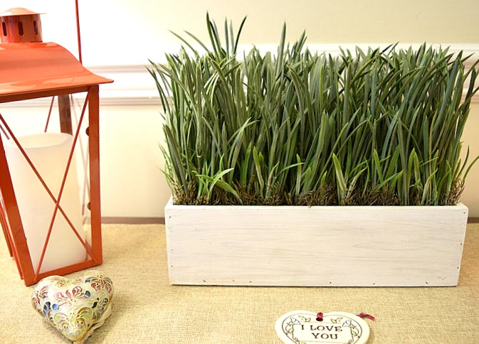 console table with red lanterns, heart ornaments and faux grass in a white rectangular planter
