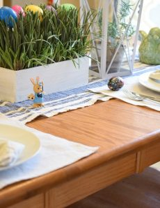 A beautiful farmhouse-style table decorated for Easter with a faux grass and Easter egg centerpiece