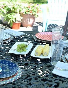 A table set with fun outdoor dinner plates, outdoor placemats, serving pieces and sterling silver dinnerware.