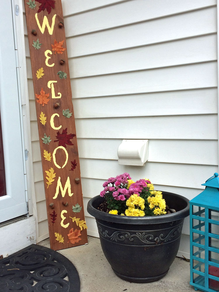 Fall porch with DIY welcome sign, blue lantern and potted mums