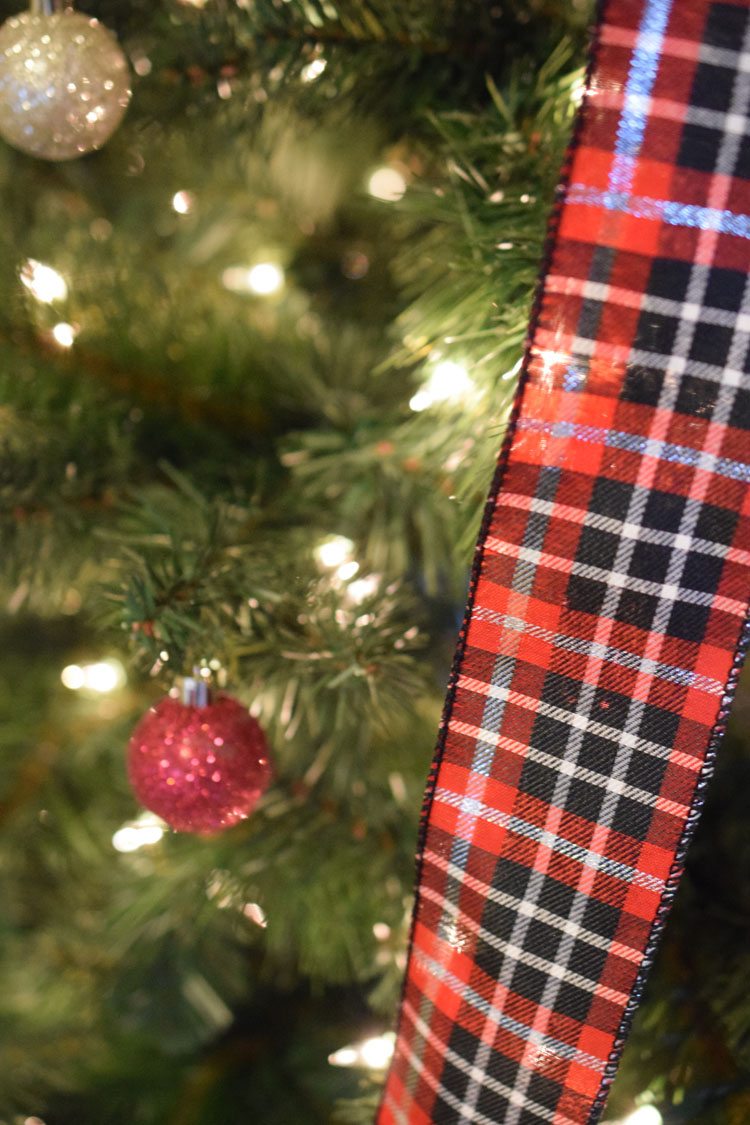 Red, white and black plaid ribbon on a faux pine Christmas tree with a glittery red ball orament