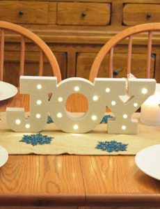 A Christmas table with silver reindeer, a burlap table runner, white lanterns and a lighted marquee joy sign
