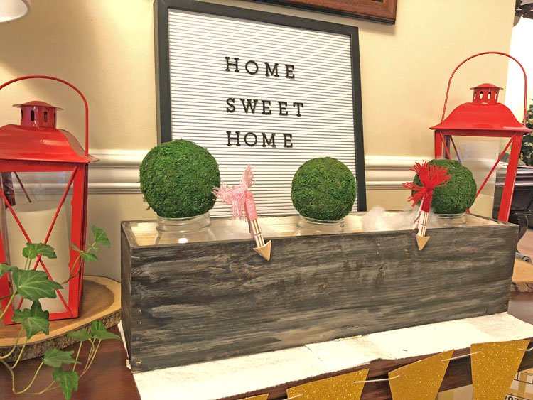 Valentine's Day console table with flower box filled with mason jars and moss balls, letter board and lanterns