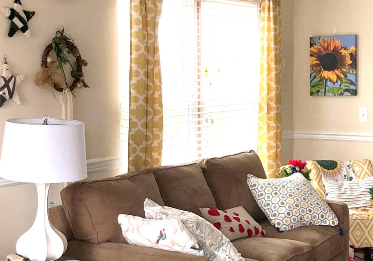 Living room with brown sofa, colorful pillows, yellow curtains and a DIY gallery wall