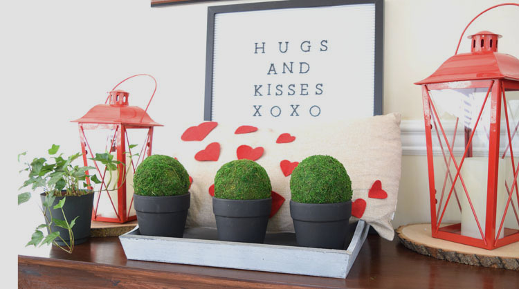 Valentne's Day console table with burlap heart pillow, red lanterns, letter board, gray trayb potted moss and English ivy