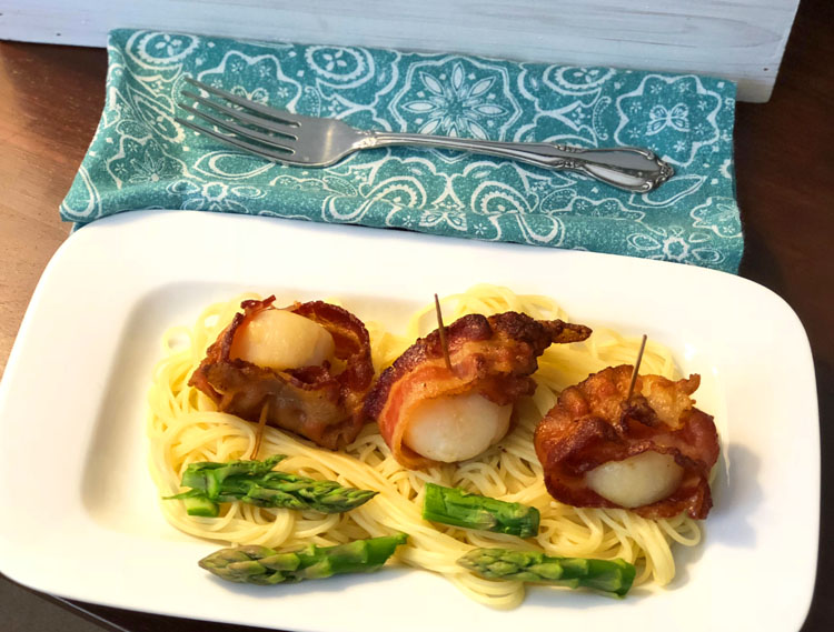 An Easter appetizer -- scallops wrapped in bacon and served with buttery angel hair pasta and fresh asparagus