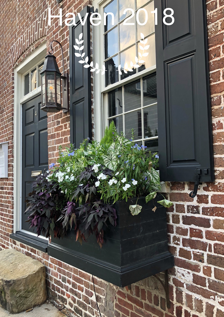 Brick home in Charleston, S.C., with a gas light, black door, black shutters and a beautiful flower box