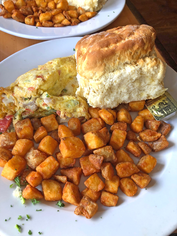 seafood omelette with scallops and shrimp, with breakfast potatoes and biscuit served at Toast restaurant in Charleston
