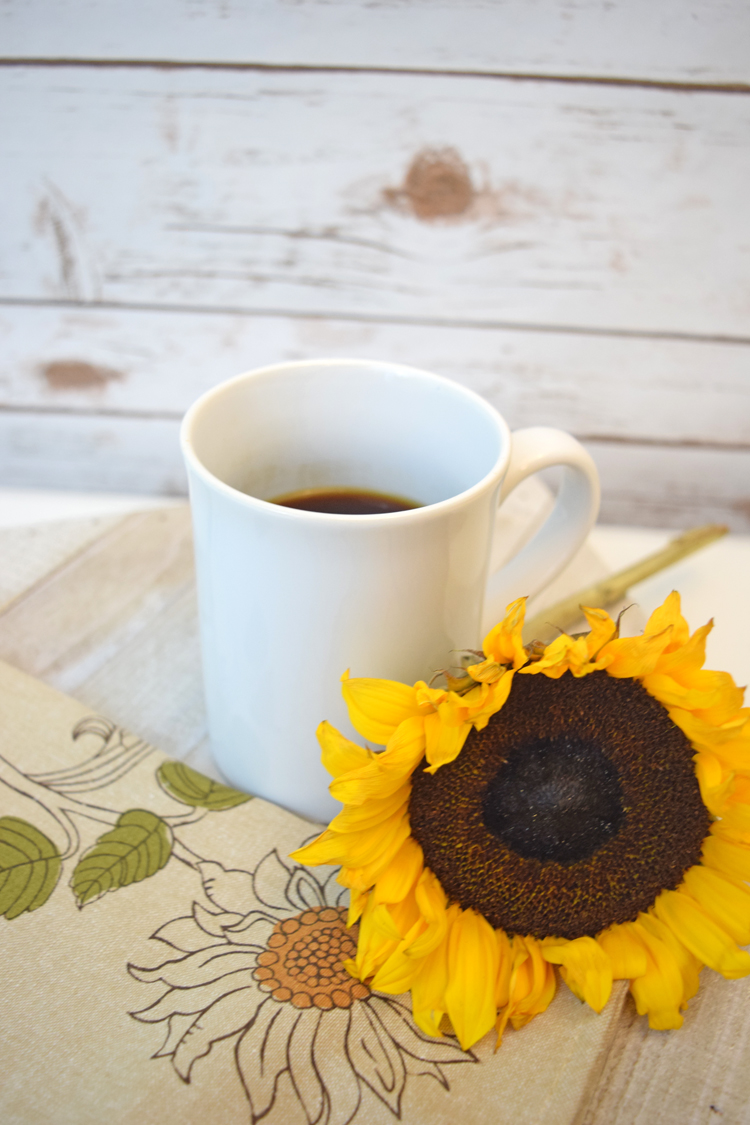 a cup of coffee with a fall sunflower against a farmhouse style wall