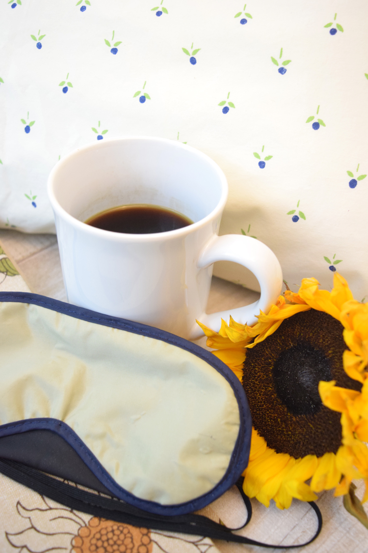 Cup of coffee with sleep mask and sunflower against a pillow