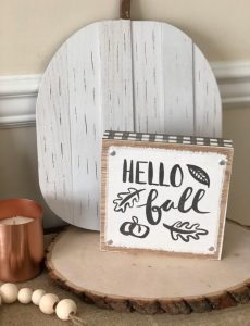 Hello sign on an autumn console table on a wood round and in front of a white wooden pumpkin
