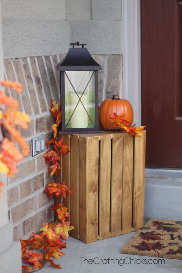 small front porch with a crate, pumpkin and black lantern