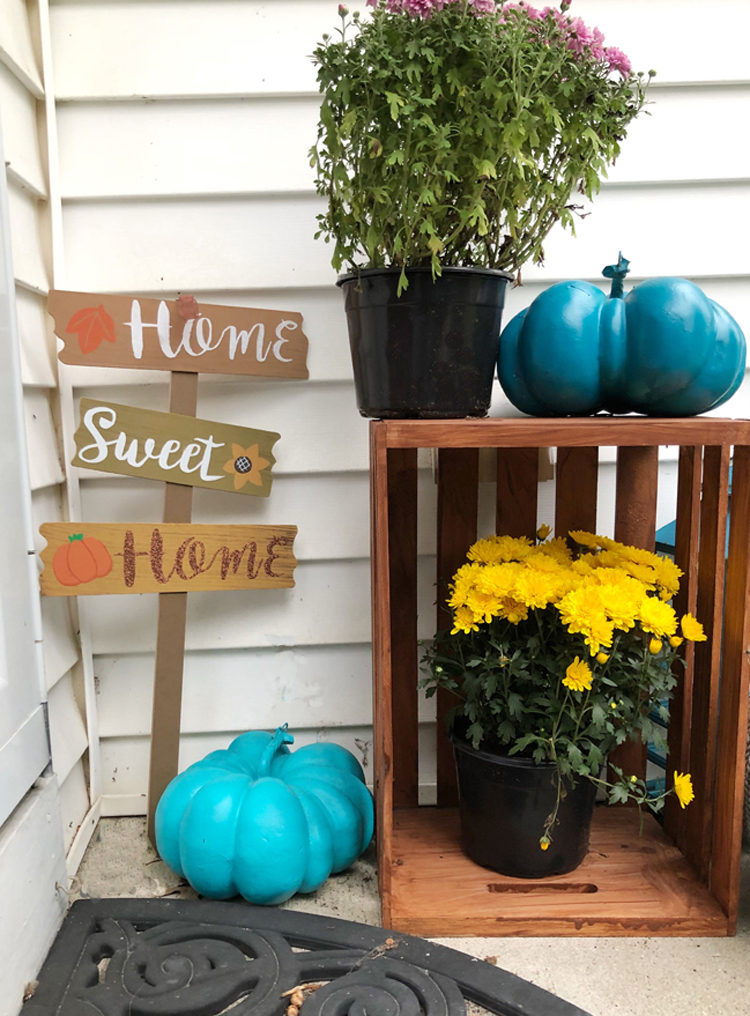 small fall front porch with home sweet home sign, wood crate, mums and lantern