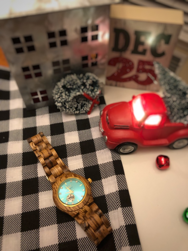 A Jord wood watch with a mini red Christmas pickup truck and Christmas tree, galvanized metal house and buffalo plaid napkin