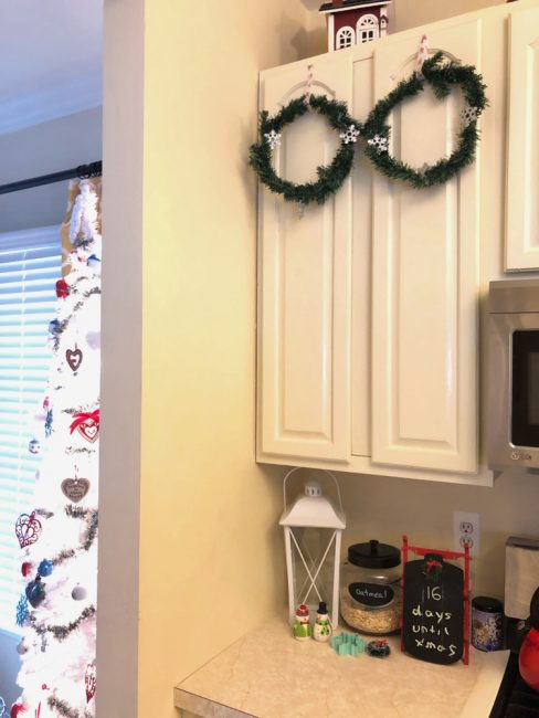 Mini wreaths from the dollar store on kitchen cabinet doors for Christmas. Plus, you won't believe the super easy way to hang these up!