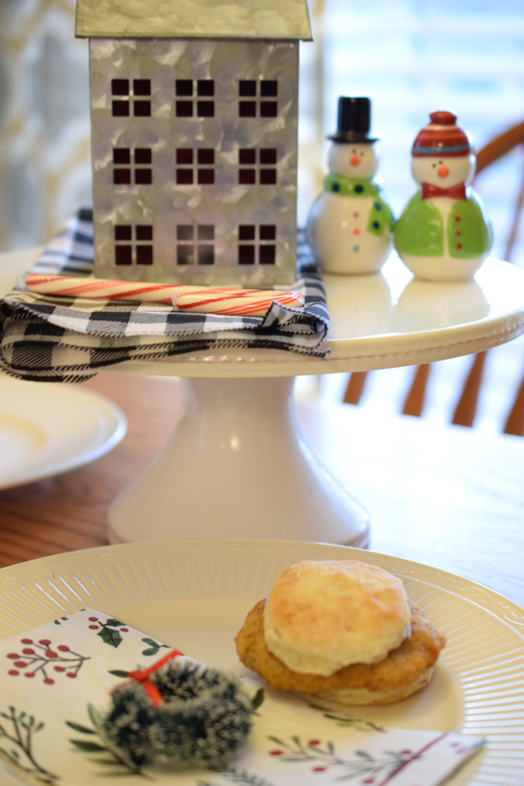 Cute raised holiday display on a Christmas table with Christmas napkins, place setting and breakfast sandwich