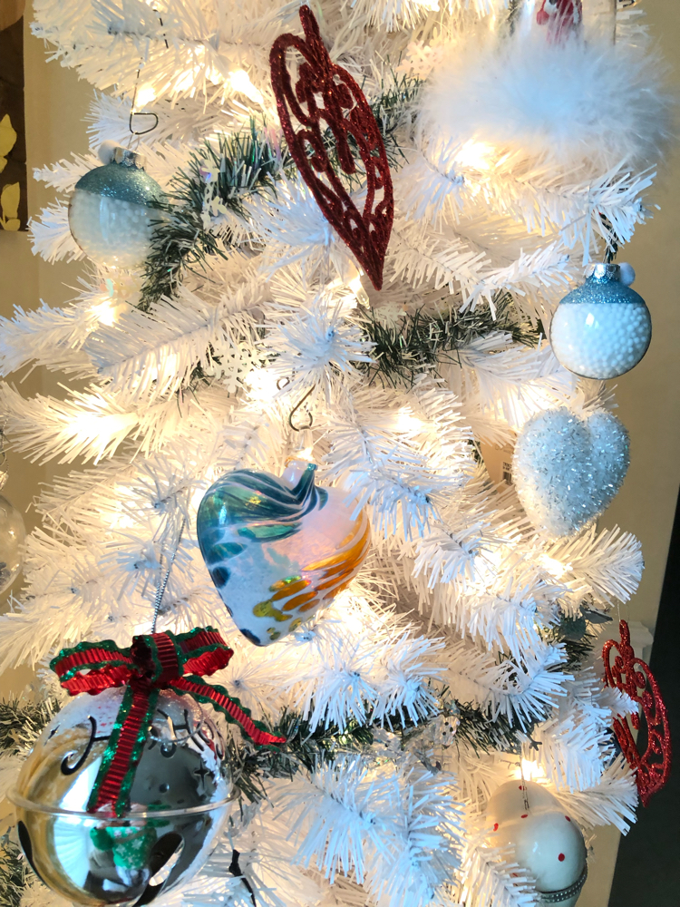 white Christmas tree with colorful heart ornaments