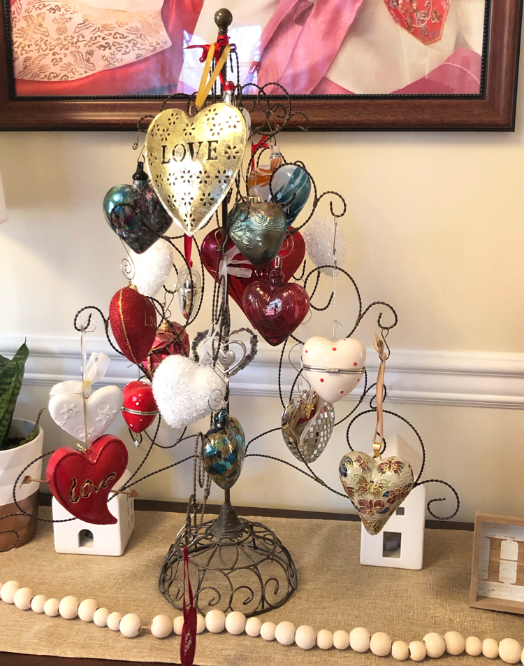 Console table decorated for Valentine's Day with a heart ornament tree, heart ornaments, white ceramic houses and a potted snake plant