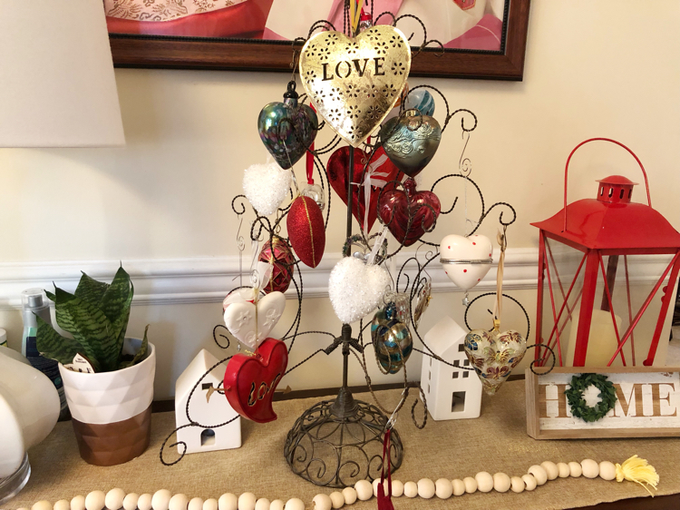 A Valentine's Day console table with a heart ornament tree filled with heart ornaments. Also on the table are a wooden bead garland, a potted snake plant , a home sign and a red lantern.