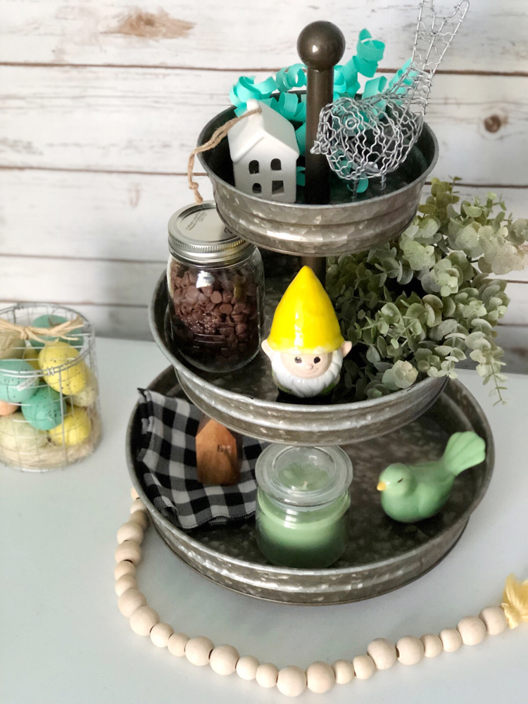 A galvanized tiered tray for spring decorated with birds, a garden gnome, miniature houses and faux greenery.