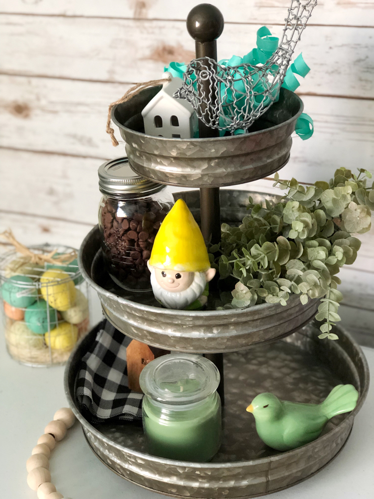 A three tiered galvanized tray decorated for spring with faux greenery, a garden gnome, ceramic and wire birds, mini houses, a buffalo plaid napkin and a candle.