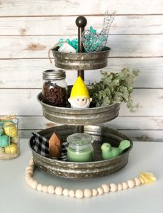A three tiered galvanized decorated for spring with faux greenery, a garden gnome, ceramic and wire birds, mini houses, a buffalo plaid napkin and a candle.