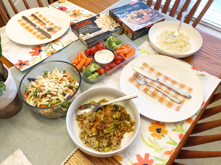 Pretty spring table set with spring green table runner, floral placemats , salad, fresh veggies and delicious Stouffer's and Lean Cuisine foods.