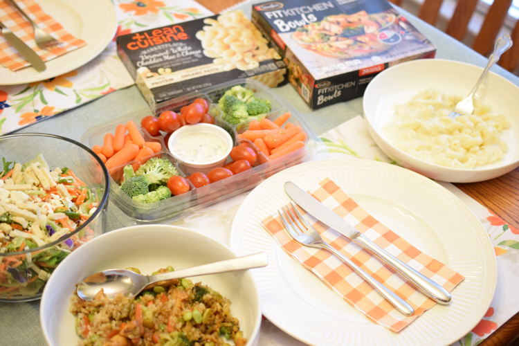A pretty spring table set with fresh vegetables, salad and Lean Cuisine and Stouffer's entrees.
