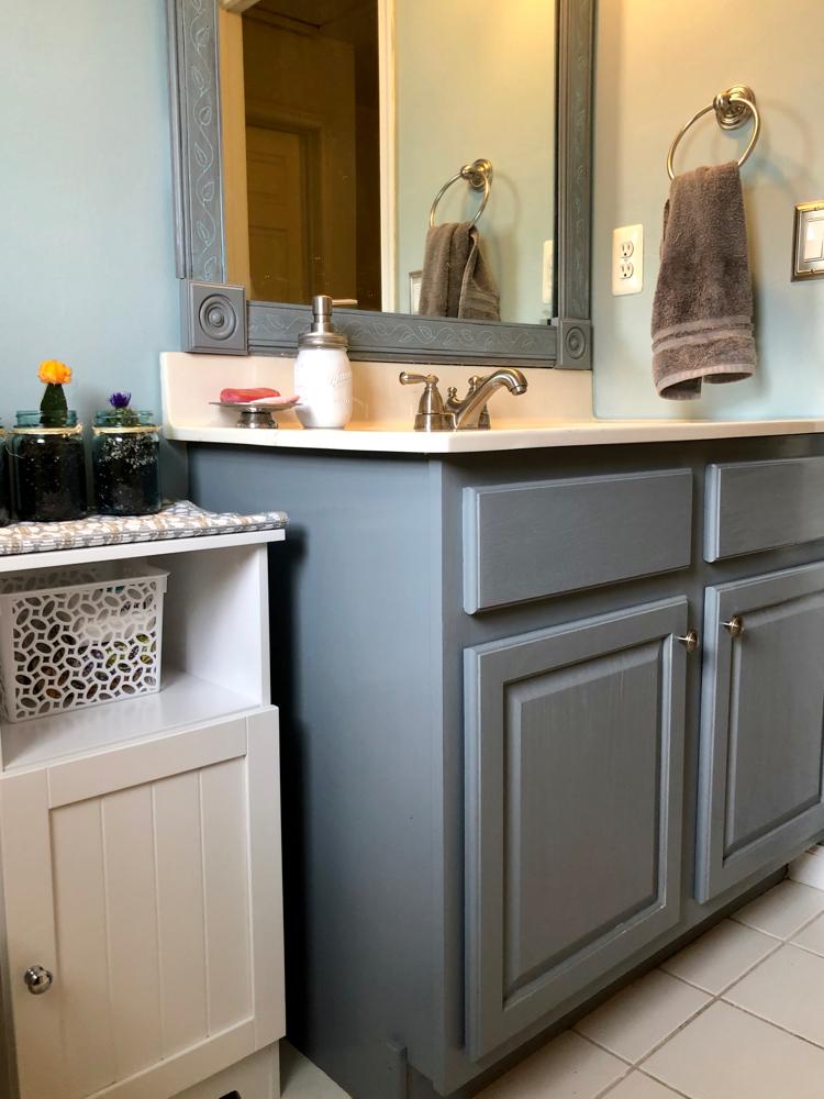 A blue bathroom with a gray painted bathroom cabinet, DIY bathroom mirror and mason jar succulents..
