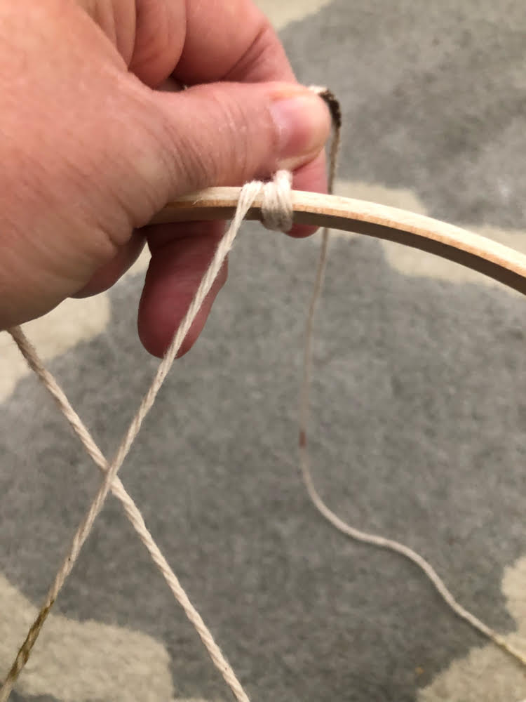 wrapping yarn around an embroidery hoop to create a dream catcher