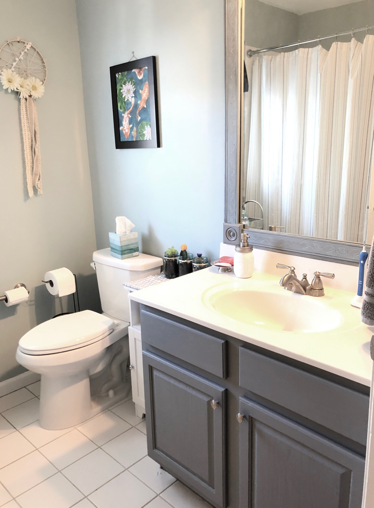 Updated bathroom with DIY wall art, painted vanity and DIY mirror frame and Yarsmouth Blue Benjamin Moore paint.