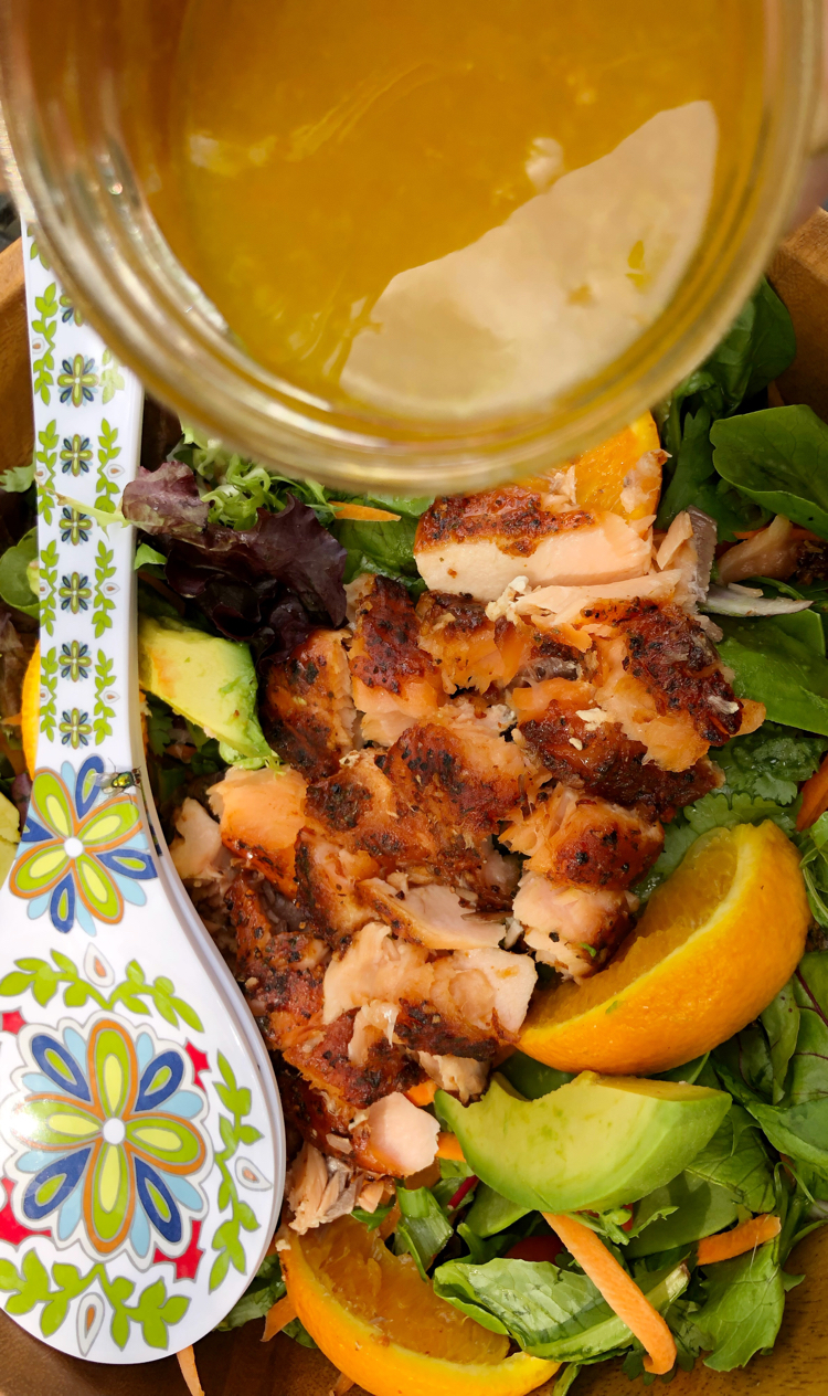 A fresh green salad with grilled orange ginger salmon, oranges, avocado and a homemade salad dressing.