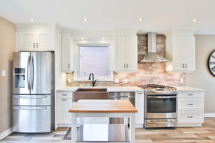 modern kitchen with a butcherblock counter and brick backsplash