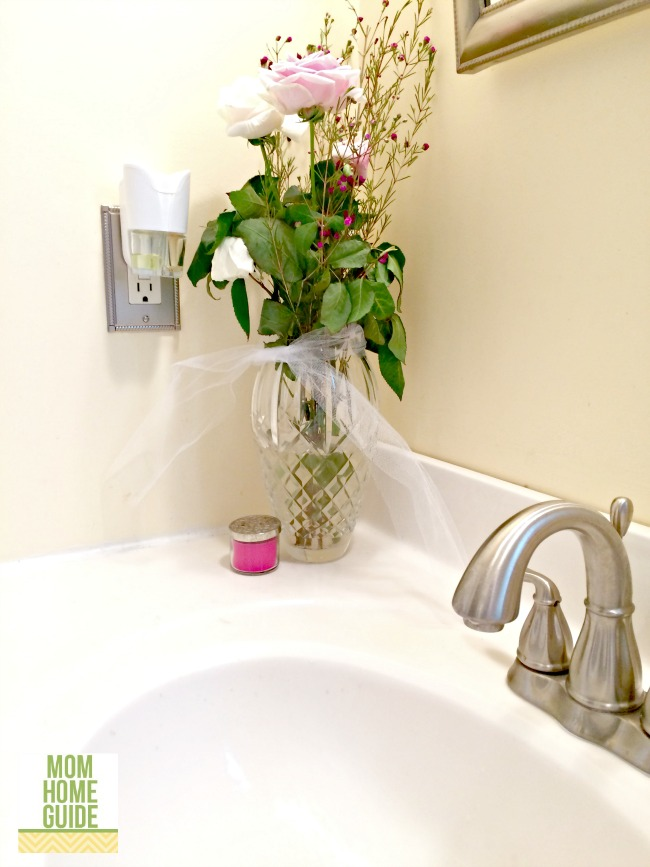 fresh flowers and scented oil in bathroom