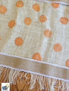 Fringed and painted burlap table runner edged with burlap ribbon
