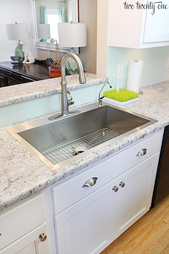White kitchen with stainless steel accents and gray and white laminate counters