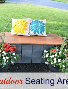 DIY outdoor seating area with a DIY cinder block and wood bench and stenciled pillows