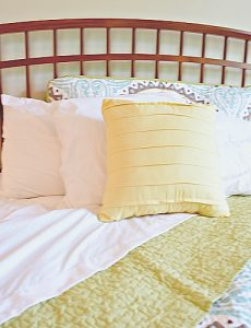 Beautiful curved head board in a master bedroom with blue and gray quilt