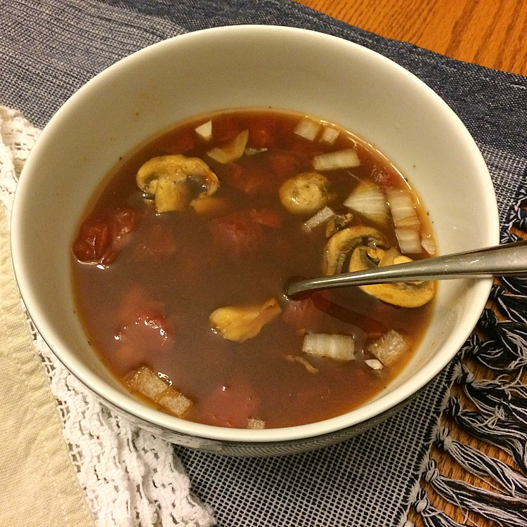 Homemade vegetable soup with diced tomatoes, beans and mushrooms